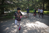 A woman playing jianzi with a shuttlecock during morning exercises in Beihai Park an imperial garden to the northwest of the Forbidden City in...