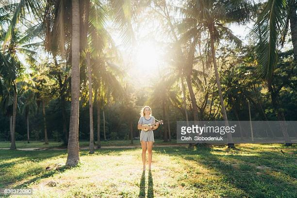Woman playing on ukulele in the palm tree forest