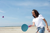 Portrait of a young woman playing paddle ball at the beach