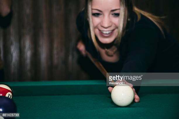 Woman playing pool billard in a bar, smiling
