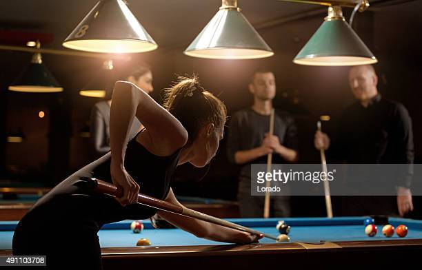 woman playing pool with group of friends