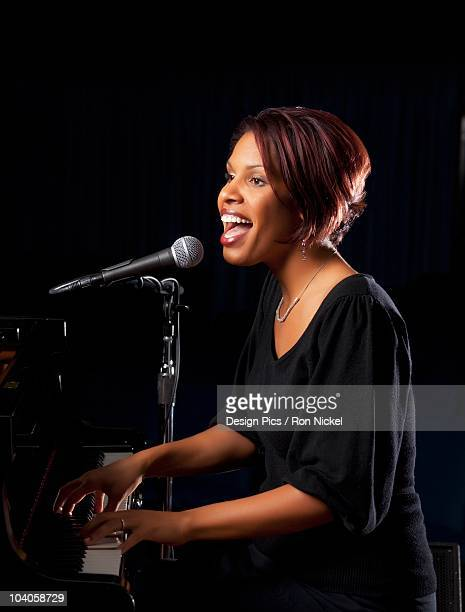A Woman Playing The Piano And Singing Into A Microphone