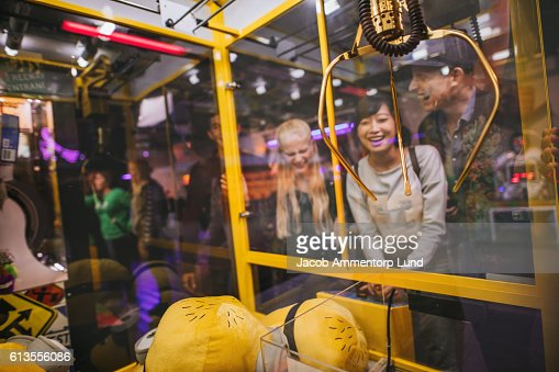Woman playing toy grabbing game with friends : Stock Photo