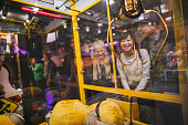 Happy young woman playing toy grabbing game with friends at amusement park.