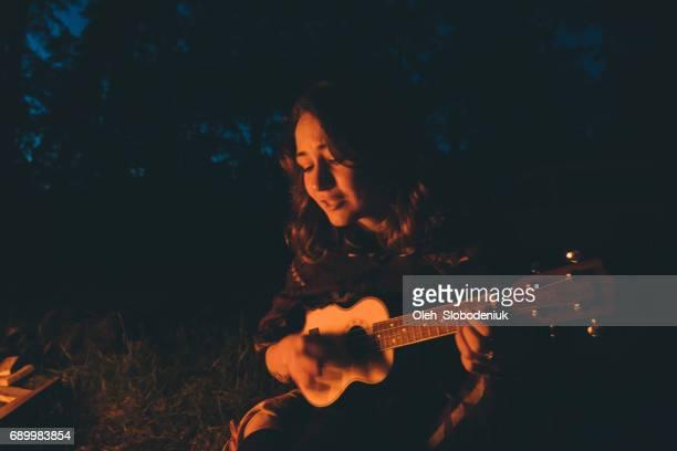Femme jouant ukulélé près du feu de camp dans la forêt pendant la nuit