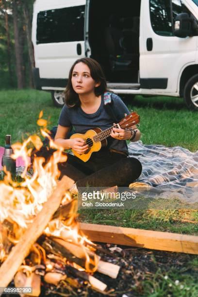 Femme jouant ukulélé près du feu de camp dans la forêt