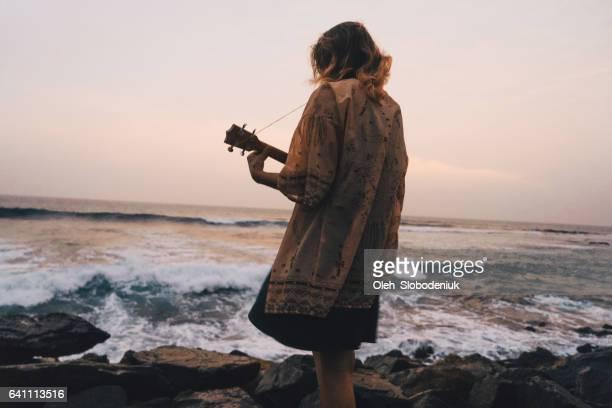 Femme jouant ukulélé près de la mer