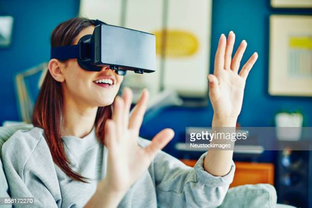 Woman playing video game with virtual reality simulator at home