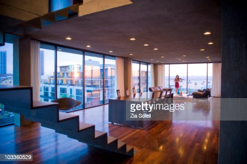 Woman playing violin in modern condo living room : Stock Photo