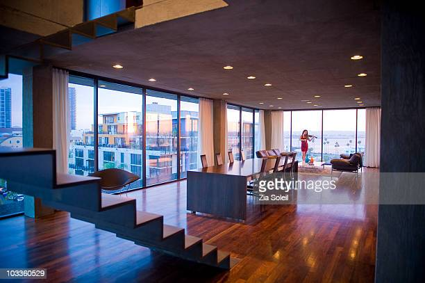 Woman playing violin in modern condo living room