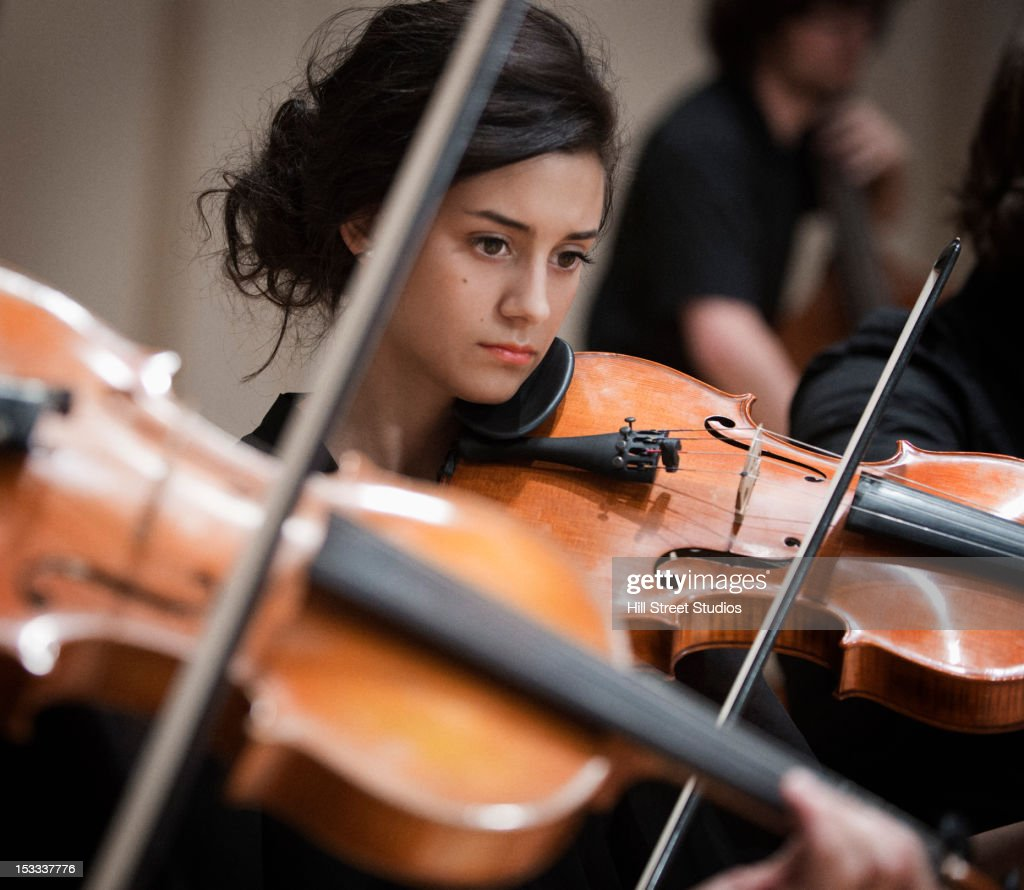 Woman playing violin in orchestra
