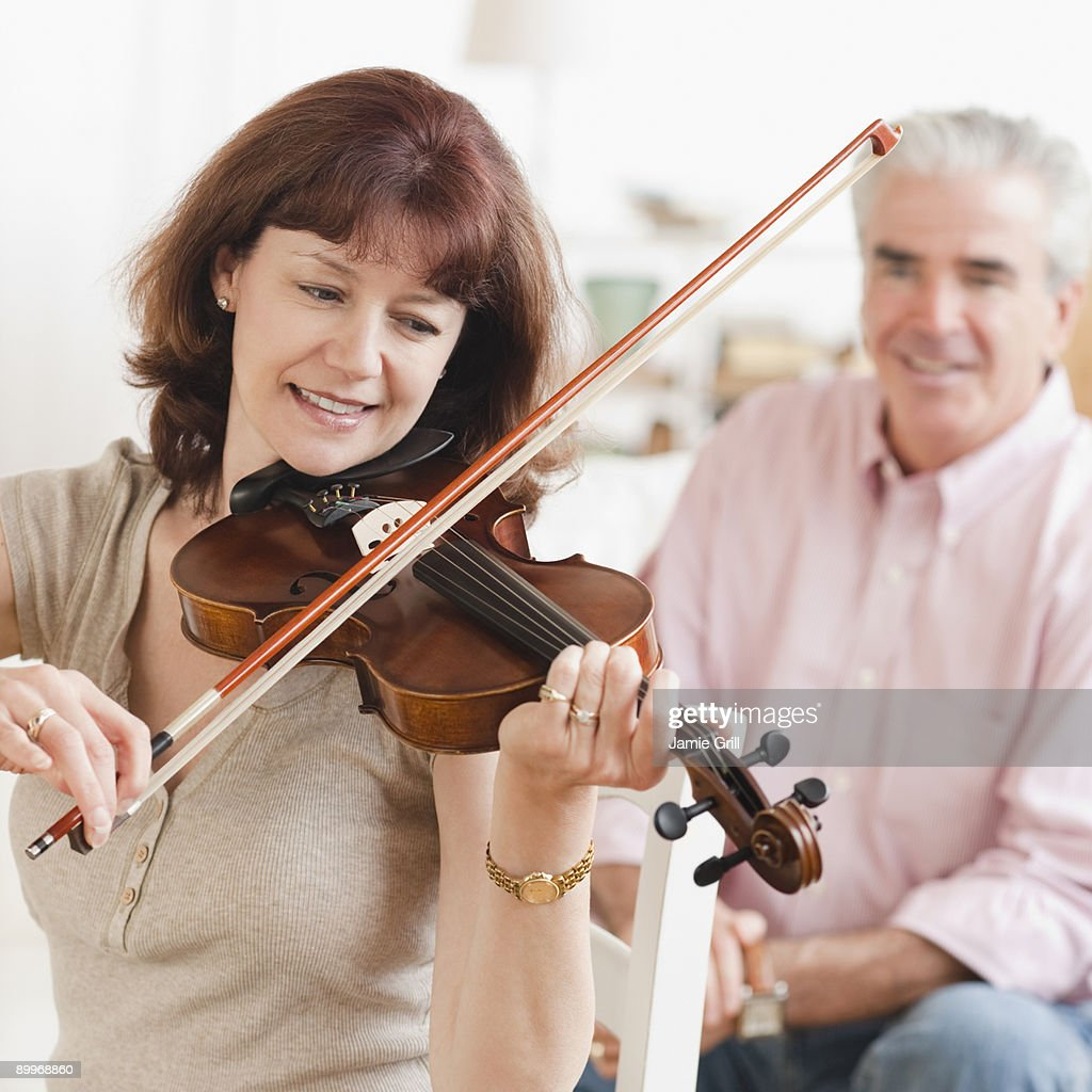 Woman playing violin while husband watches : Stock Photo