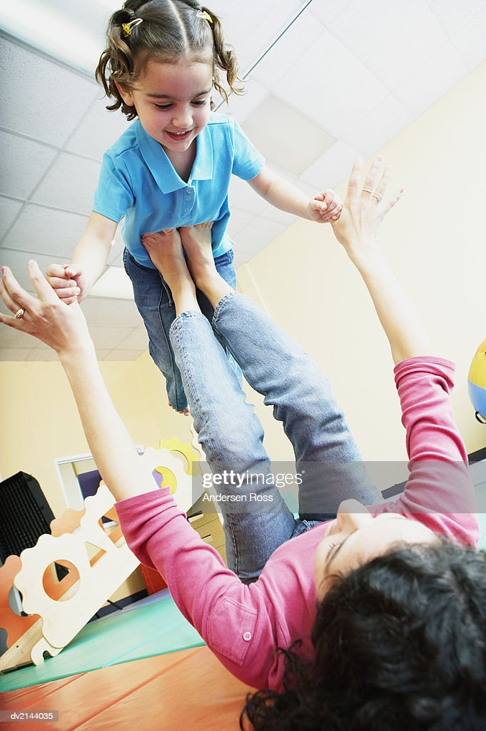 Woman Playing with a Young Girl in a Nursery : Stock Photo
