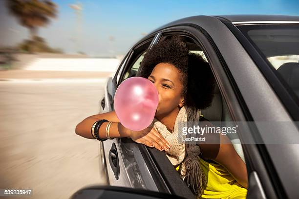 Woman playing with chewing gum on a road trip