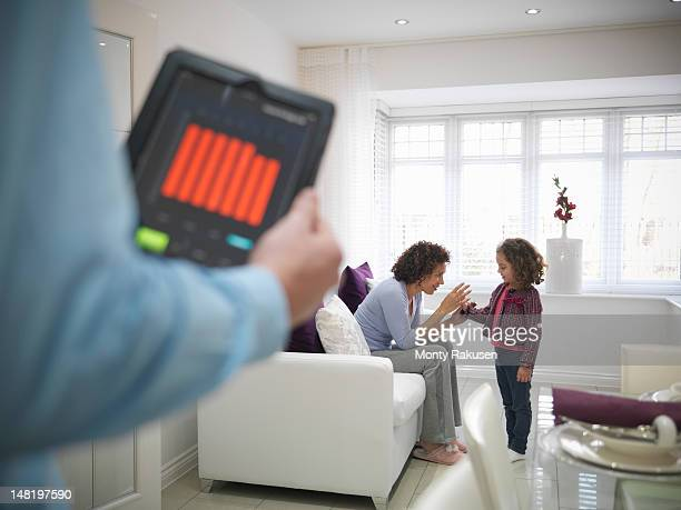 Woman playing with daughter as father checks energy application on digital tablet