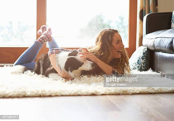 Woman playing with dog at home.