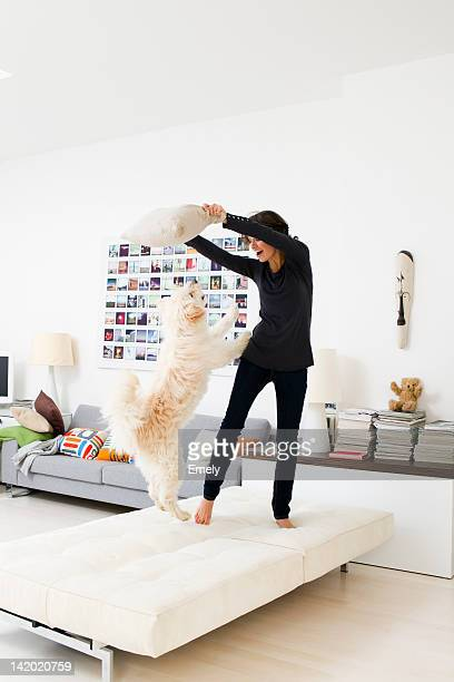 Woman playing with dog in living room