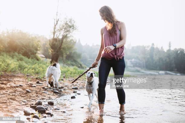 Woman Playing With Dogs at River