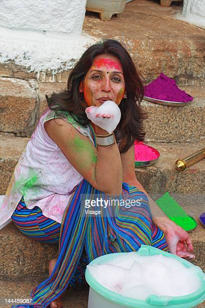 Woman playing with foam, face smeared with holi