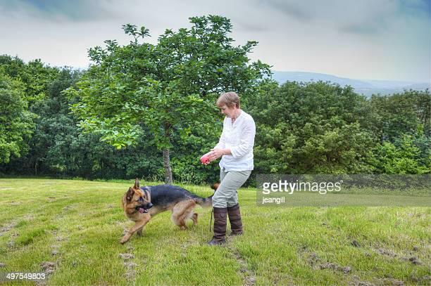 Woman playing with German Shepherd Dog