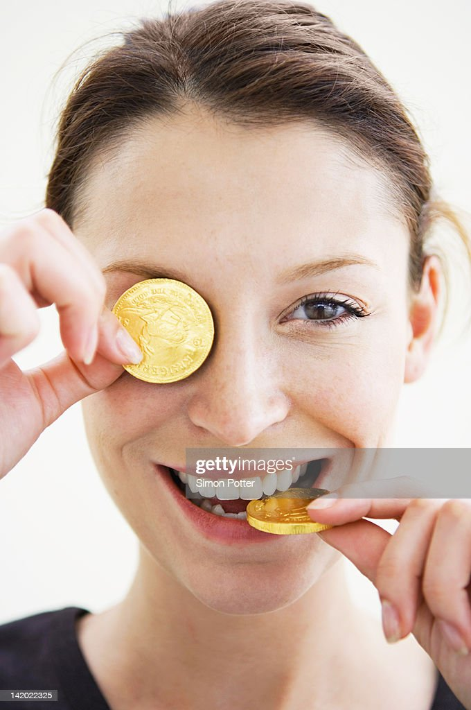 Woman playing with gold coins : Stock Photo