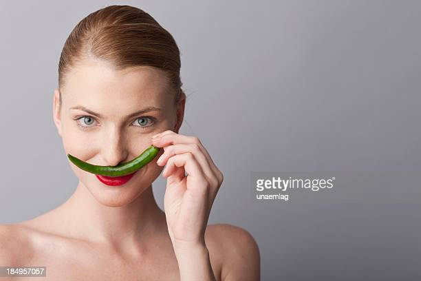 woman playing with green hot pepper