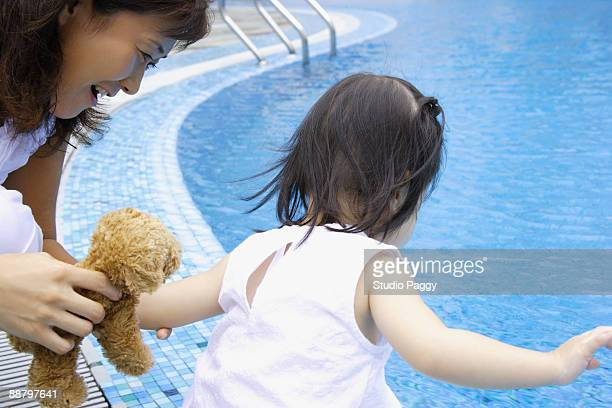 Woman playing with her daughter at the poolside