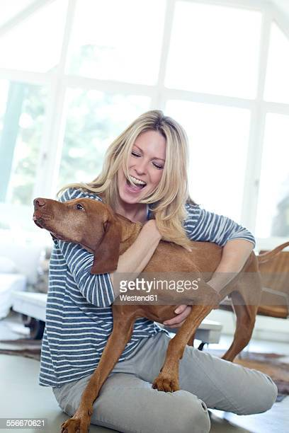 Woman playing with her dog at home