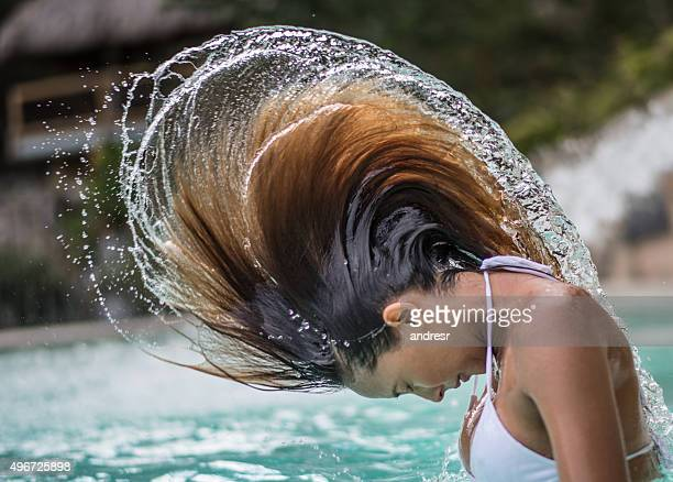 Woman playing with her hair in a swimming pool