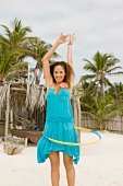 Woman playing with plastic toy hoop on beach