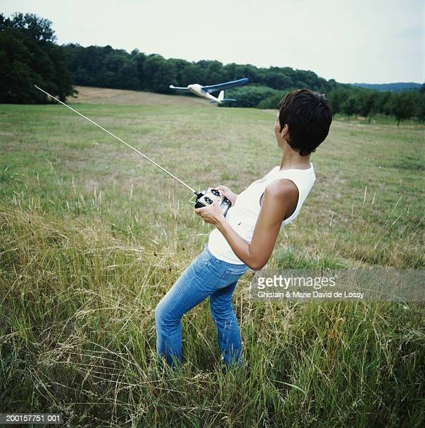 Woman playing with remote control plane in field, side view