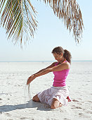 Woman playing with sand beneath palm tree (Palma sp.), smiling
