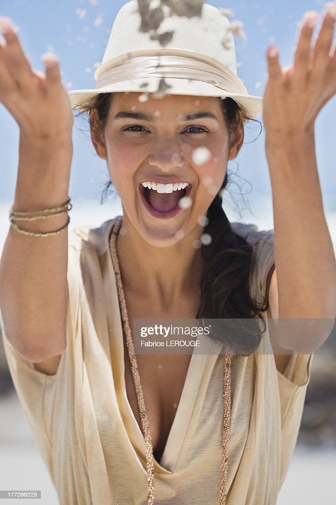 Woman playing with sand on the beach : Stock Photo