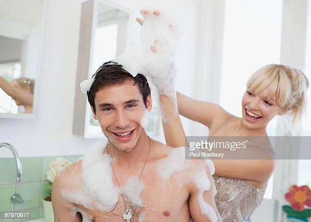 Donna giocando con sapone suds su uomo in bagno