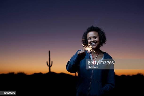 Femme jouant avec Cierge magique dans le désert