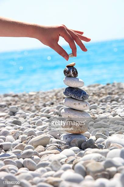 woman playing with ston pile on beach