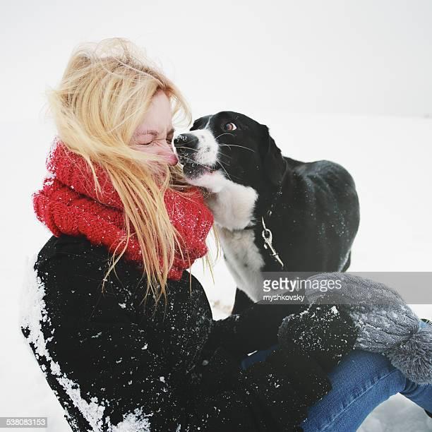 Donna giocare con il Cane nella neve fresca