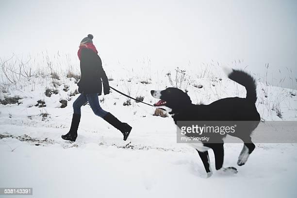 Frau spielen mit dem Hund im Neuschnee