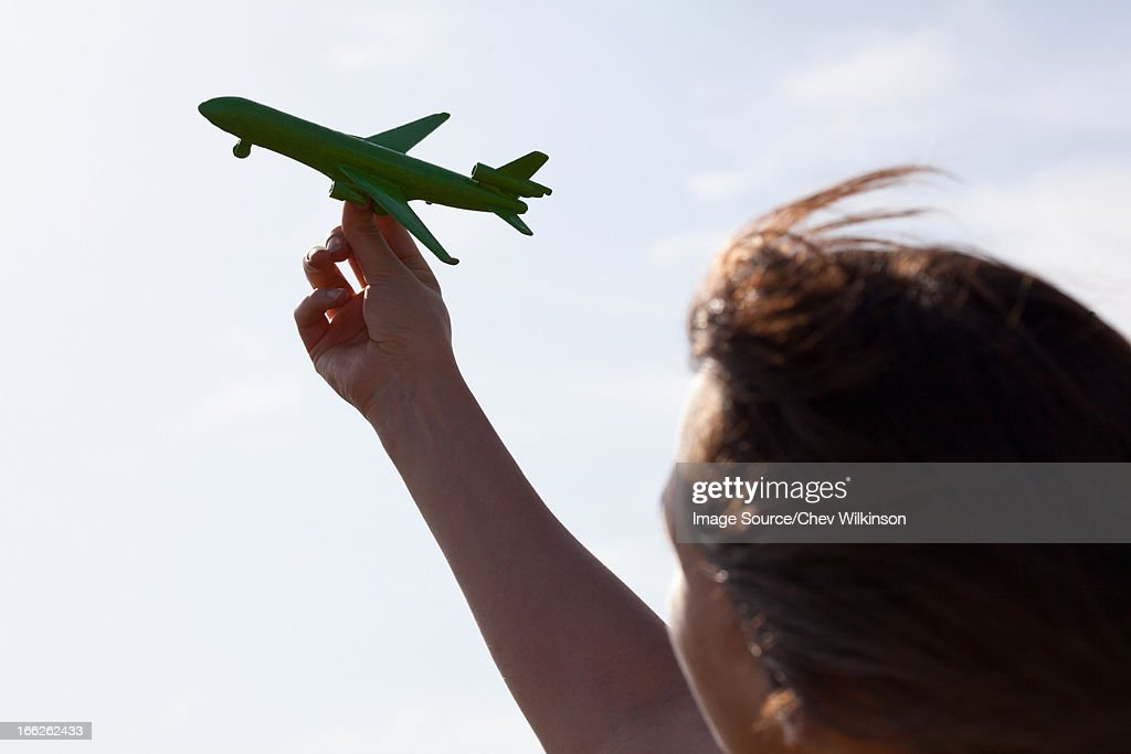 Woman playing with toy airplane : Stock Photo