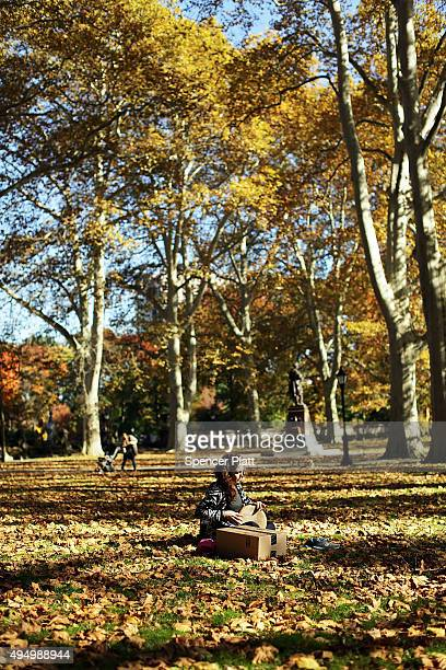 A woman plays a drum surrounded by fallen leaves as autumn foliage fills the trees of Prospect Park on October 30 2015 in the Brooklyn borough of New...