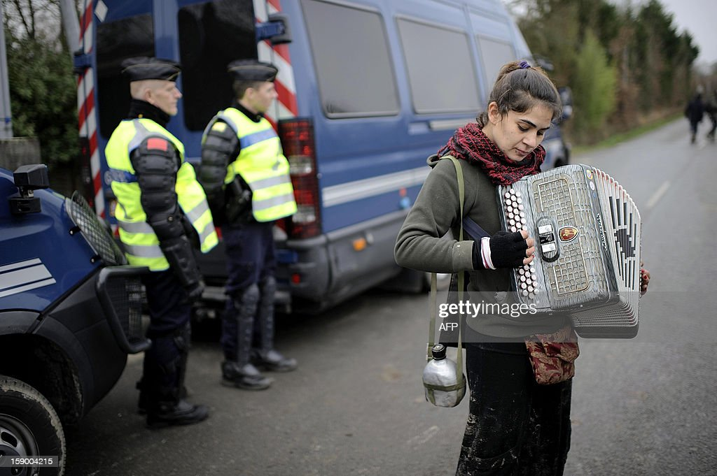 A woman plays accordeon next to French gendarmes during a music festival organized by opponents against a project of international airport on January 5, 2013 in Notre-Dame-des-Landes, western France. The project was signed in 2010 and the international airport is supposed to open in 2017 near the city of Nantes.