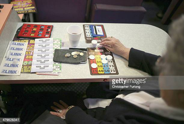 A woman plays Bingo at Carlton Bingo Hall in Orrell Park as the Chancellor George Osborne announces tax breaks for Bingo halls on March 19 2014 in...