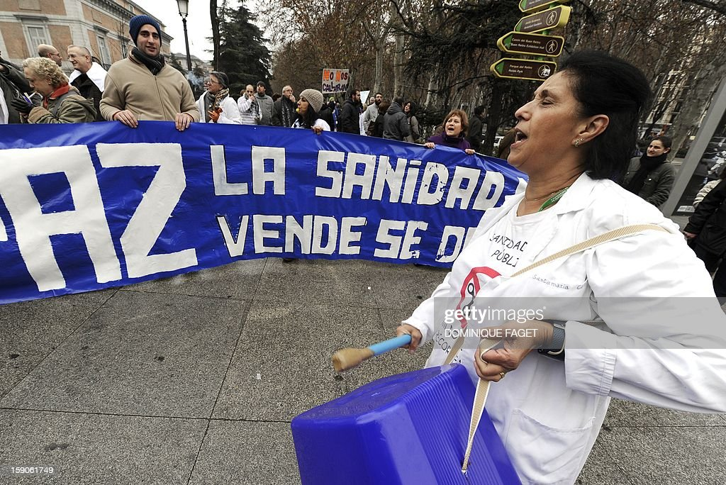 A woman plays drums on a plastic bucket as she takes part in a demonstration organized by Spanish health workers to denounce budget cuts and privatisations in health services, in Madrid on January 7, 2013.