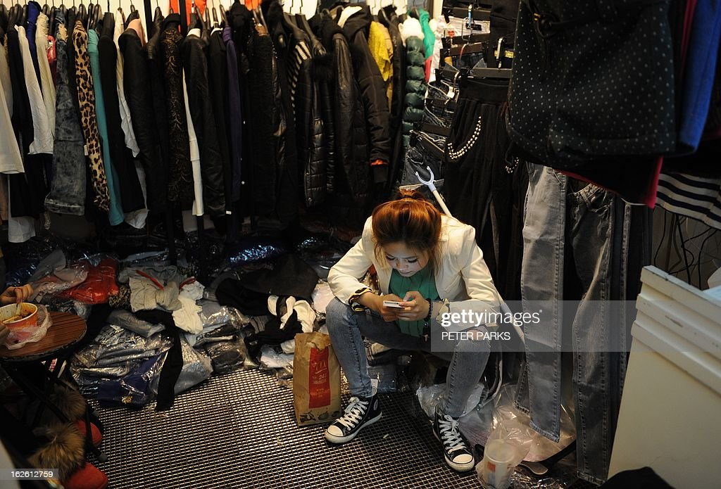 A woman plays on her phone in a shop in a wholesale clothing market in Shanghai on February 25, 2013. China's manufacturing growth hit a four-month low in February but remained positive, British banking giant HSBC said on February 25, noting that the world's second-biggest economy was still recovering slowly. AFP PHOTO/Peter PARKS