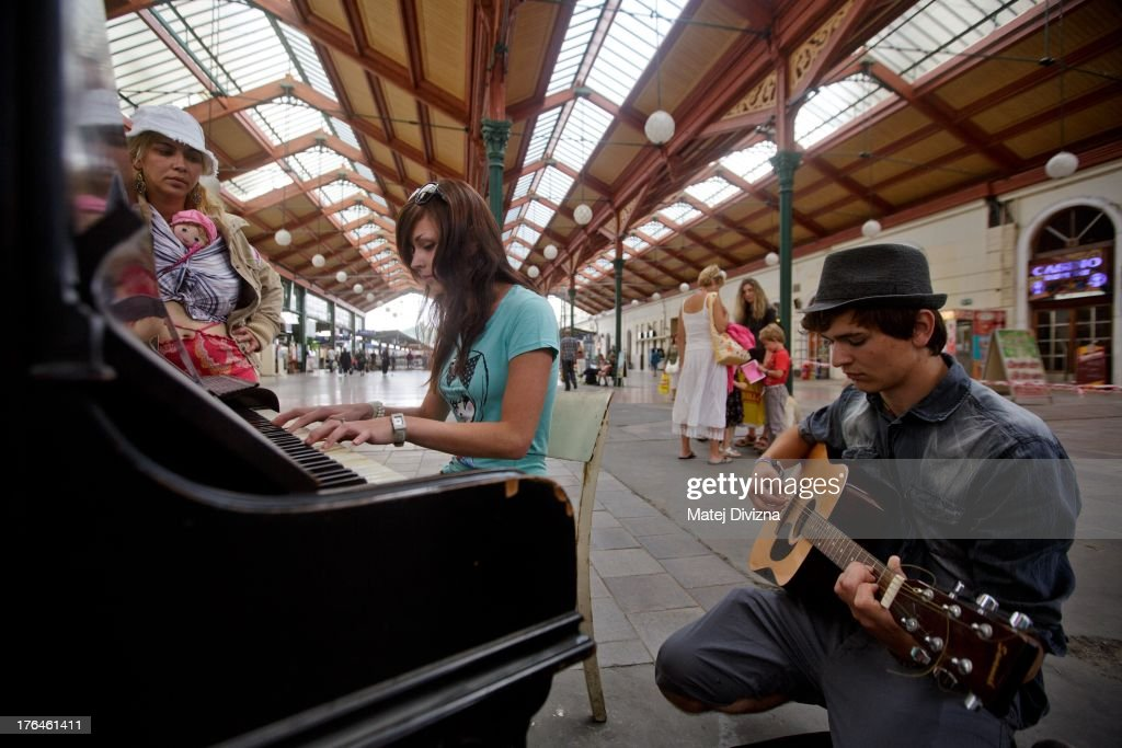 A woman plays piano as a man plays guitar during the first day of the 'Pianos on the street' project at Masaryk railway station on August 13, 2013 in Prague, Czech Republic. The project, by Prague cafe owner Ondrej Kobza, started in Prague today. Kobza placed pianos in five spots in the city centre for random passers-by to play. Similar projects run worldwide.