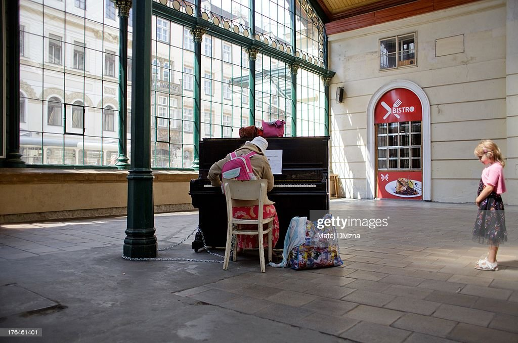 A woman plays piano as girl listens during the first day of the 'Pianos on the street' project at Masaryk railway station on August 13, 2013 in Prague, Czech Republic. The project, by Prague cafe owner Ondrej Kobza, started in Prague today. Kobza placed pianos in five spots in the city centre for random passers-by to play. Similar projects run worldwide.