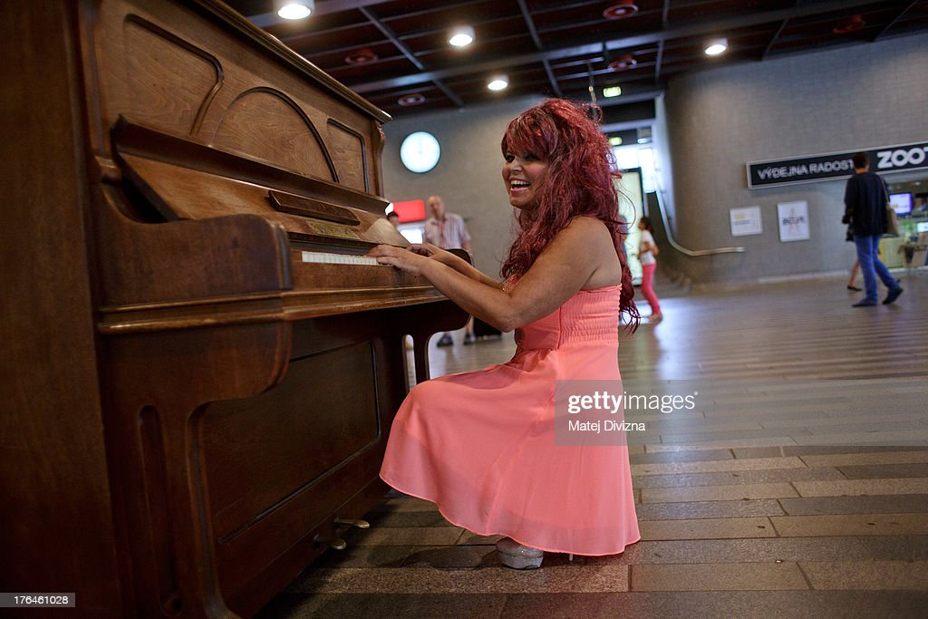 A woman plays piano during the first day of the 'Pianos on the street' project at the main railway station on August 13, 2013 in Prague, Czech Republic. The project, by Prague cafe owner Ondrej Kobza, started in Prague today. Kobza placed pianos in five spots in the city centre for random passers-by to play. Similar projects run worldwide.