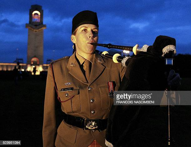 A woman plays the bagpipes during the Anzac day in tribute of Australians and New Zealanders soldiers killed in combat shows the cemetery of the...