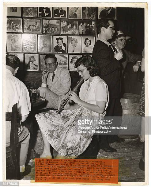 A woman plays the recorder at Julius in Greenwich Village New York New York mid 1940s Behind her is the bar's wall of celebrity portraits 'A girl...
