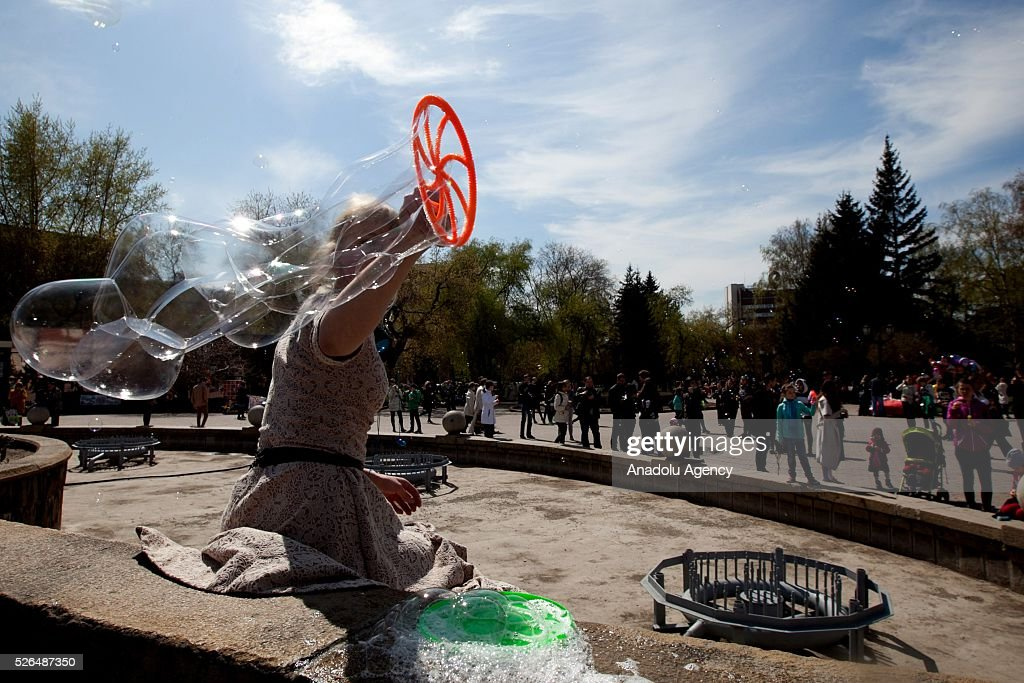 Woman plays with soap bubbles during the Dreamflash soap bubble festival at the Pervomaisky Square in Novosibirsk, Russia, on April 30, 2016.